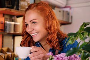 Close up portrait of redhead female barista drinks coffee.